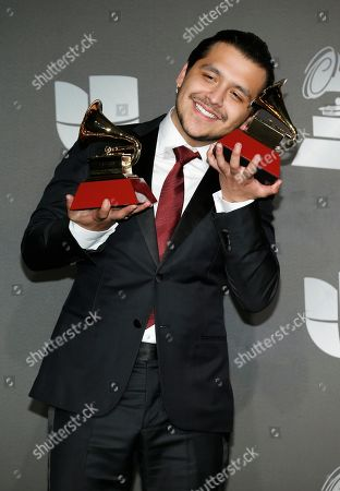 """Christian Nodal poses in the press room with the awards for best ranchero/mariachi album for """"Ahora,"""" and best regional song for """"No Te Contaron Mal,"""" at the 20th Latin Grammy Awards, at the MGM Grand Garden Arena in Las Vegas"""