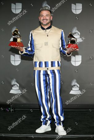 """Pedro Capo poses in the press room with the awards for song of the year for """"Calma,"""" and best urban fusion/performance for """"Calma (Remix),"""" at the 20th Latin Grammy Awards, at the MGM Grand Garden Arena in Las Vegas"""