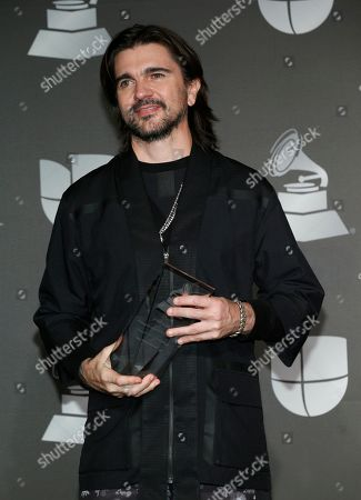 Juanes poses in the press room with the person of the year award at the 20th Latin Grammy Awards, at the MGM Grand Garden Arena in Las Vegas
