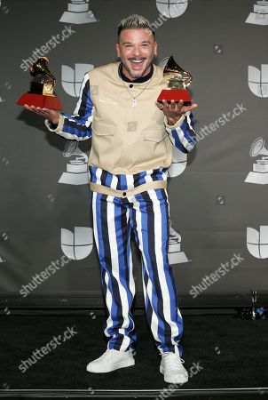"""Pedro Capo poses in the press room with the awards for song of the year for """"Calma"""" and best urban fusion/performance for """"Calma (Remix)"""" at the 20th Latin Grammy Awards, at the MGM Grand Garden Arena in Las Vegas"""