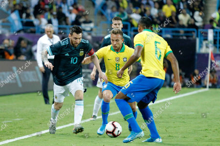 Brazil player Alex Sandro (R) and Arthur Melo (C) in action against Argentine player Lionel Messi (L) during the International Friendly match between Al-Brazil and Argentine at King Saud University Stadium, Al-Riyadh, Saudi Arabia,15 November 2019.