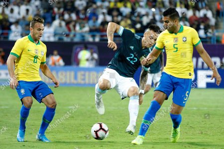 Brazil player Casemiro (R) and Arthur Melo (L) in action against Argentine player Lautaro Martinez (c) during the International Friendly match between Al-Brazil and Argentine at King Saud University Stadium, Al-Riyadh, Saudi Arabia,15 November 2019.