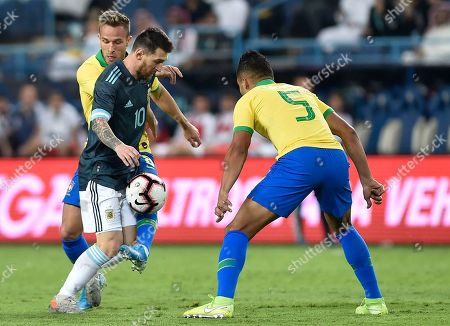 Argentina's Lionel Messi, center, fights for the ball with Brazil's Arthur, left, and Brazil's Casimiro during a friendly soccer match between Brazil and Argentina at King Fahd stadium in Riyadh, Saudi Arabia