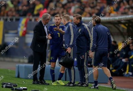 Sweden's Sebastian Larsson, center, speaks to Sweden's coach Jan Andersson, left, as he exits the pitch after an injury during the Euro 2020 group F qualifying soccer match between Romania and Sweden on the National Arena stadium in Bucharest, Romania
