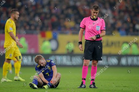 Referee Daniele Orsato tells Sweden's Sebastian Larsson to exit the pitch after an injury during the Euro 2020 group F qualifying soccer match between Romania and Sweden on the National Arena stadium in Bucharest, Romania