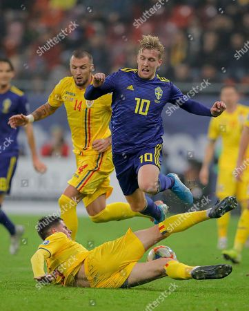 Sweden's Emil Forsberg. top, is tackled by Romania's Tudor Baluta during the Euro 2020 group F qualifying soccer match between Romania and Sweden on the National Arena stadium in Bucharest, Romania