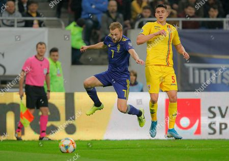 Sweden's Sebastian Larsson, left, challenges for the ball with Romania's Ionut Nedelcearu, right, during the Euro 2020 group F qualifying soccer match between Romania and Sweden on the National Arena stadium in Bucharest, Romania