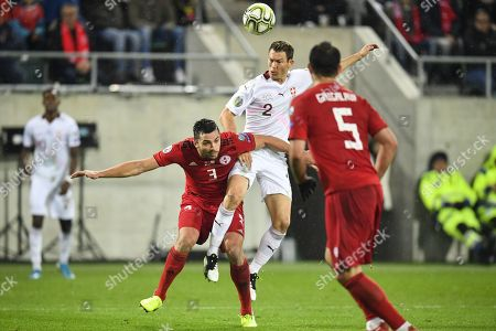 Switzerland's defender Stephan Lichtsteiner, center, fights for the ball with Georgia's Davit Khocholava, left, during the UEFA Euro 2020 qualifying Group D soccer match between Switzerland and Georgia at the Kybunpark stadium in St. Gallen, Switzerland, 15 November 2019.