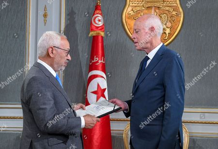 In this photo provided by the Tunisian Presidency, Tunisian President Kais Saied, right, speaks with President of the Islamist party Ennahda and new Tunisian National Assembly house speaker Rached Ghannouchi at the presidential palace in Carthage near Tunis, Tunisia