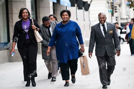Former Georgia House Democratic Leader Stacey Abrams, center, departs from an event at the National Press Club, in Washington
