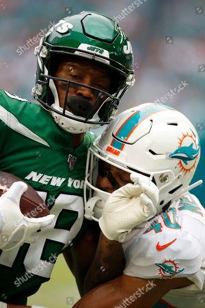 Demaryius Thomas, Nik Needham. New York Jets wide receiver Demaryius Thomas (18) tackles Miami Dolphins defensive back Nik Needham (40) during an NFL football game, in Miami Gardens, Fla. The Dolphins won 26-18