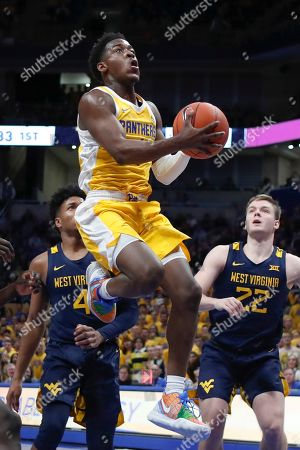 Pittsburgh's Xavier Johnson, center, shoots between Sean McNeil (22) and Miles McBride (4) during the first half of an NCAA college basketball game, in Pittsburgh