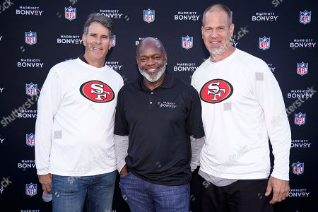 Former San Francisco 49ers Steve Bono, left, Joe Nedney, right, and NFL Hall of Fame running back Emmitt Smith pose for a photo after coaching members of Marriott Bonvoy who bid their points to participate in the exclusive moments masterclass held at the San Francisco 49ers training facility on in Santa Clara, Calif