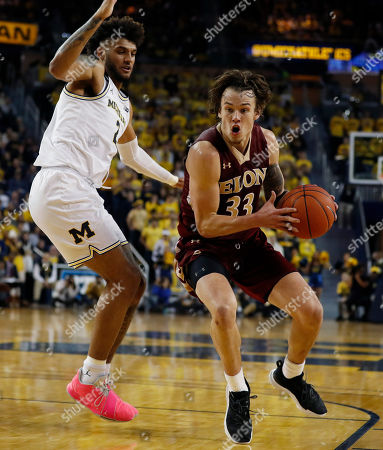 Elon forward Simon Wright is defended by Michigan forward Isaiah Livers (2) during the first half of an NCAA college basketball game against Michigan, in Ann Arbor, Mich