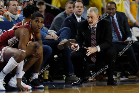 Elon head coach Mike Schrage, right, talks with guards Christian Scott, left, and Hunter McIntosh during the second half of an NCAA college basketball game, in Ann Arbor, Mich