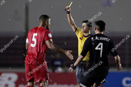 Referee Ricardo Moreno of Costa Rica shows a yellow card to Panama's Roman Torres, left, during a CONCACAF Nations League soccer match against Mexico at the Rommel Fernandez stadium in Panama City