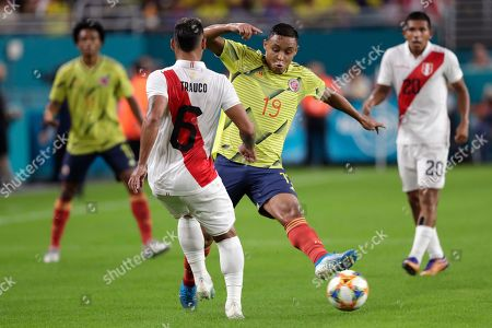Luis Muriel, Miguel Trauco. Colombia forward Luis Muriel (19) passes as Peru defender Miguel Trauco (6) defends during the first half of an international friendly soccer match, in Miami Gardens, Fla