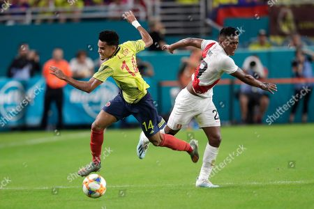 Luis Díaz, Pedro Aquino. Colombia forward Luis Díaz (14) and Peru midfielder Pedro Aquino (23) go for the ball during the first half of an international friendly soccer match, in Miami Gardens, Fla