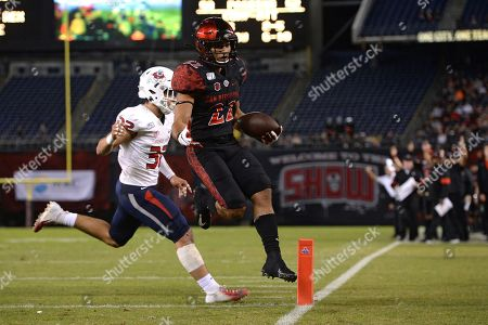 San Diego State running back Chase Jasmin (22) scores a touchdown ahead of Fresno State defensive back Evan Williams during the first half of the NCAA college football game, in San Diego