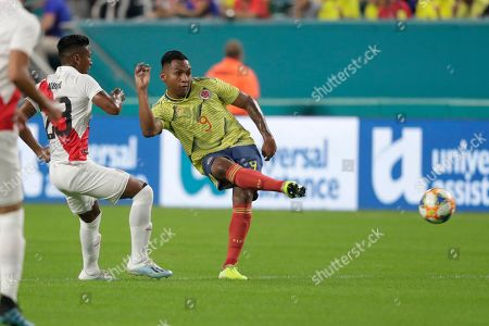 Colombia forward Radamel Falcao (9) passes the ball as Peru midfielder Pedro Aquino (23) looks on during the first half of an international friendly soccer match, in Miami Gardens, Fla