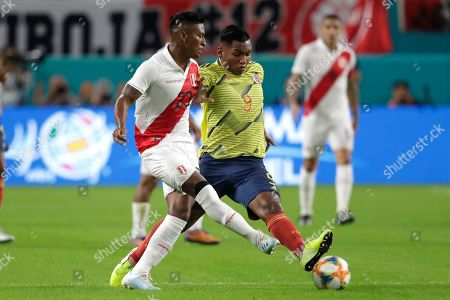 Peru midfielder Pedro Aquino, left, and Colombia forward Radamel Falcao (9)bro for the ball during the first half of an international friendly soccer match, in Miami Gardens, Fla