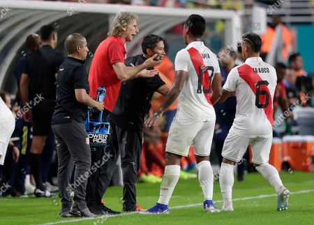 Stock Image of Peru head coach Ricardo Gareca, second from left, talks with midfielder Renato Tapia (13) during the first half of an international friendly soccer match against Colombia, in Miami Gardens, Fla
