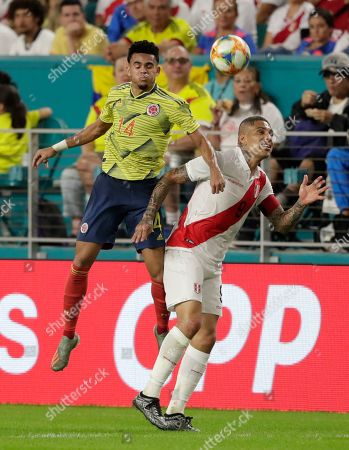 Colombia forward Luis Díaz (14) and Peru forward Paolo Guerrero (9) head the ball during the first half of an international friendly soccer match, in Miami Gardens, Fla