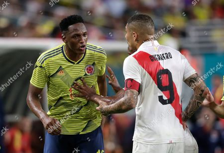 Colombia defender Yerry Mina, left, has words with Peru forward Paolo Guerrero (9) during the first half of an international friendly soccer match, in Miami Gardens, Fla