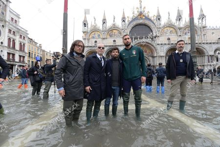 Italy's soccer team manager Gianluca Vialli (R-4) and Italy's goalkeeper Gianluigi Donnarumma (R-2) stand in water in St. Mark's Square during a solidarity visit to Venice following the exceptional high water that brought the city to its knees, in Venice, northern Italy, 16 November 2019. Four days ago, the Italian lagoon city experienced its worst flooding in more than 50 years.