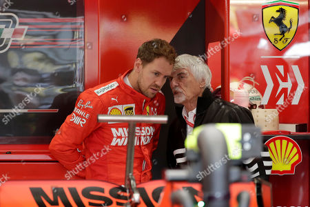 Former Formula One boss Bernie Ecclestone, right, talks with Ferrari driver Sebastian Vettel, of Germany, before the third free practice session for the Formula One Brazil Grand Prix auto race at the Interlagos race track in Sao Paulo, Brazil
