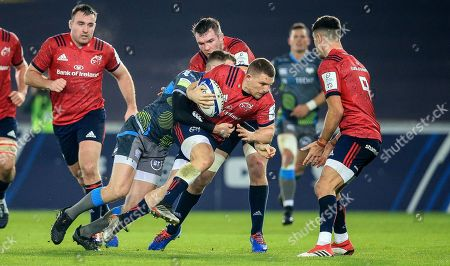 Stock Photo of Ospreys vs Munster. Munster's Andrew Conway tackled by Thomas Williams of Ospreys