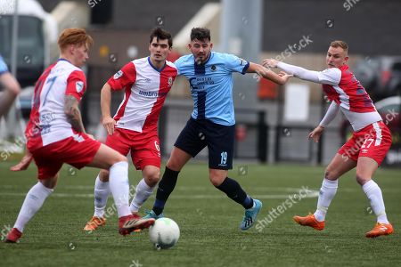 Stock Image of Institute vs Linfield. Institute's Joseph McCready with Linfield's Christopher Casement, Jimmy Gallagher and Andrew Mitchell