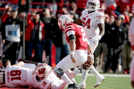 Chris Orr, Adrian Martinez, Collin Wilder, John Torchio. Nebraska quarterback Adrian Martinez (2) scores a touchdown against Wisconsin safety Collin Wilder (18)], safety John Torchio (19) and linebacker Chris Orr (54), during the first half of an NCAA college football game in Lincoln, Neb