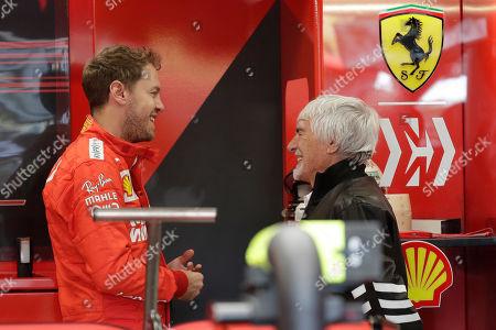 Former Formula One boss Bernie Ecclestone, right, talks with Ferrari driver Sebastian Vettel, of Germany, before the third free practice session for the Formula One Brazil Grand Prix at the Interlagos race track in Sao Paulo, Brazil