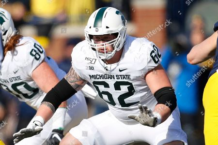 Michigan State offensive lineman Luke Campbell blocks against Michigan in the first half of an NCAA college football game in Ann Arbor, Mich