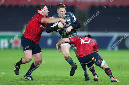 Stock Picture of Tom Williams of Ospreys is tackled by James Cronin of Munster and Tyler Bleyendaal of Munster
