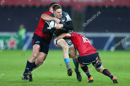 Stock Photo of Tom Williams of Ospreys is tackled by James Cronin of Munster and Tyler Bleyendaal of Munster