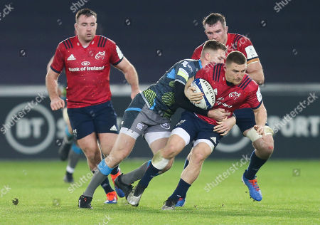 Andrew Conway of Munster is tackled by Tom Williams of Ospreys