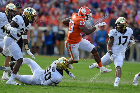 Clemson's Lyn-J Dixon (23) rushes while defended by Wake Forest's Coby Davis during the first half of an NCAA college football game, in Clemson, S.C