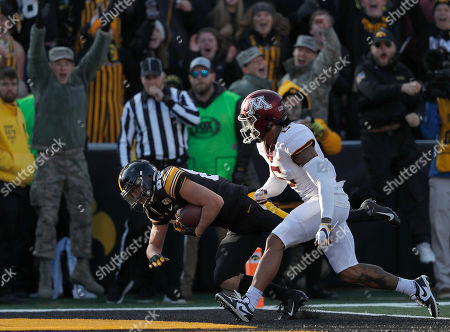 Iowa wide receiver Nico Ragaini, left, dives into the end zone for a touchdown as Minnesota defensive back Chris Williamson trails during the first half of an NCAA college football game, in Iowa City, Iowa