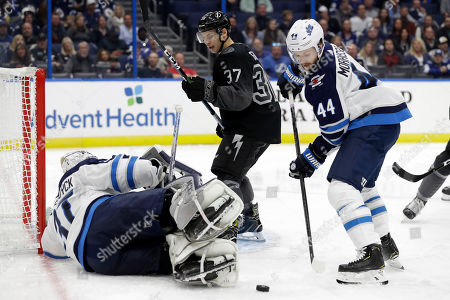 Josh Morrissey, Connor Hellebuyck, Yanni Gourde. Winnipeg Jets defenseman Josh Morrissey (44) clears the puck after Tampa Bay Lightning center Yanni Gourde (37) took a shot on goaltender Connor Hellebuyck (37) during the second period of an NHL hockey game, in Tampa, Fla