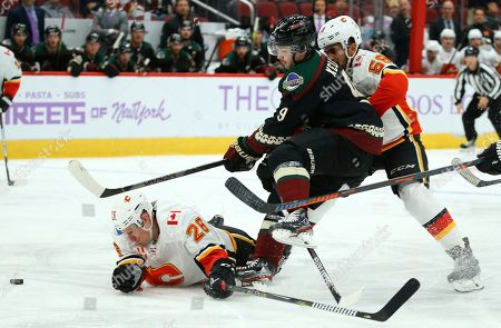Arizona Coyotes center Clayton Keller (9) gets tripped up by Calgary Flames defenseman Oliver Kylington (58) and Flames defenseman Michael Stone (26) during the second period of an NHL hockey game, in Glendale, Ariz