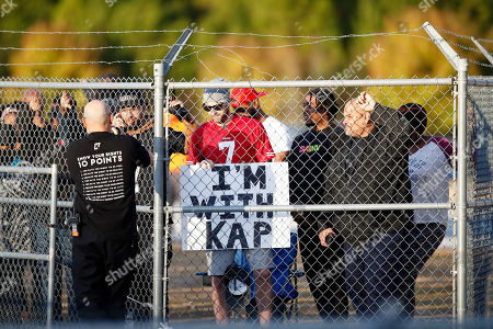 Fans watch from behind a fence as free agent quarterback Colin Kaepernick participates in a workout for NFL football scouts and media, in Riverdale, Ga