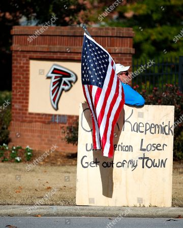 A protester holds an American flag and a sign outside of the Atlanta Falcons' training facility where free agent quarterback Colin Kaepernick was set to workout for NFL football scouts, Saturday, Nov. 16, 2019, in Flowery Branch, Ga. The workout was moved to a high school in Riverdale, Ga