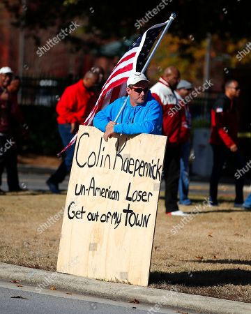 A protester holds an American flag and a sign outside of the Atlanta Falcons' training facility where free agent quarterback Colin Kaepernick was set to workout for NFL football scouts, in Flowery Branch, Ga. The workout was moved to a high school in Riverdale, Ga