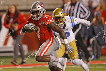 Utah running back Devonta'e Henry-Cole (7) outruns UCLA defensive back Elijah Gates, rear, in the second half during an NCAA college football game, in Salt Lake City
