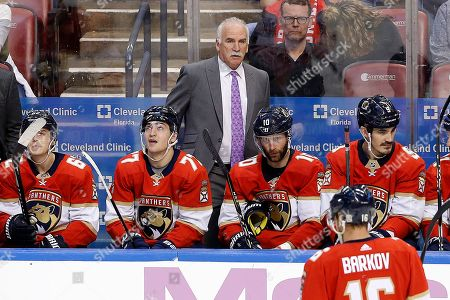Florida Panthers head coach Joel Quenneville, top center, looks on during the third period of his team's win over the New York Rangers in an NHL hockey game, in Sunrise, Fla