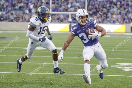 Kansas State Wildcats running back James Gilbert (34) carries the ball as West Virginia Mountaineers safety Kerry Martin Jr. (15) gives chase during the NCAA Football Game between the West Virginia Mountaineers and the Kansas State Wildcats at Bill Snyder Family Stadium in Manhattan, Kansas