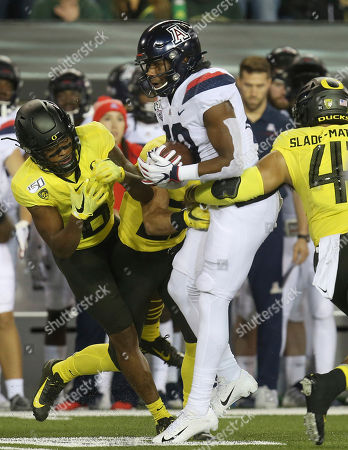 Arizona's Jamarye Joiner, center, is tackled by Oregon's Deommodore Lenoir, left, and Isaac Slade-Matautia during the first quarter of an NCAA college football game, in Eugene, Ore