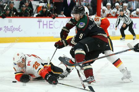 Arizona Coyotes center Clayton Keller (9) gets tripped up by Calgary Flames defenseman Oliver Kylington, right, and Flames defenseman Michael Stone (26) during the second period of an NHL hockey game, in Glendale, Ariz